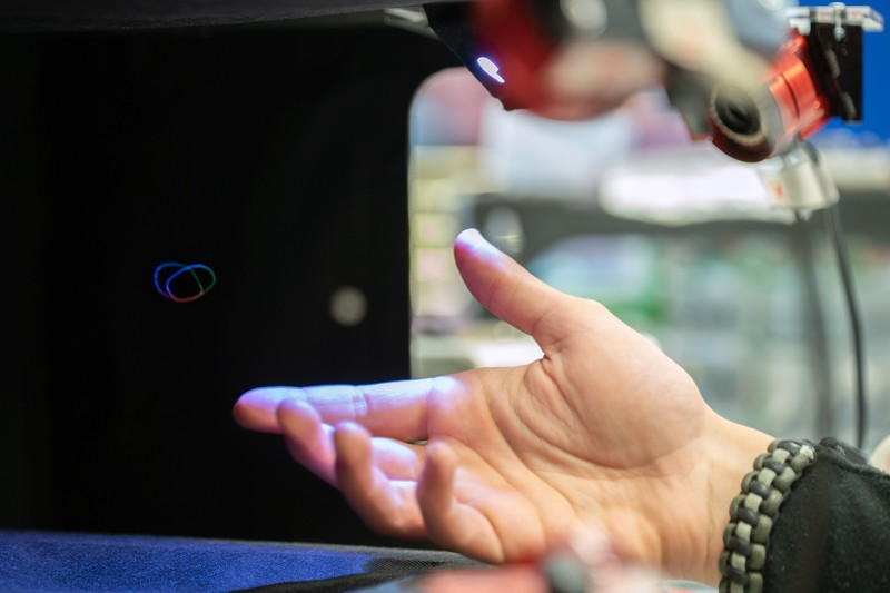 A hand reaches out to a 3D volumetric display