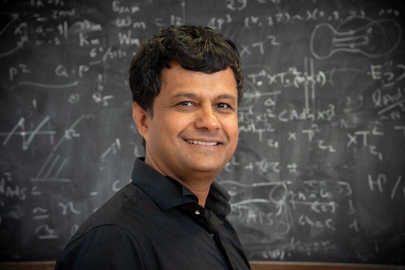 Atish Dabholkar standing in front of a blackboard covered in equations.