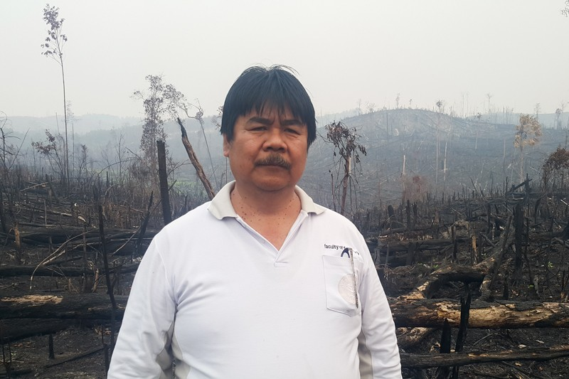 Bambang Hero Saharjo in front of a burned area