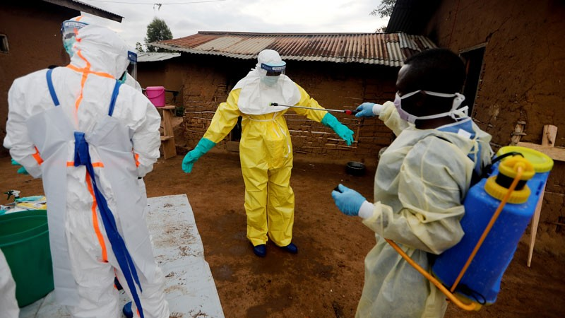 Kavota Mugisha Robert, a healthcare worker, who volunteered in the Ebola response, decontaminates his colleague.