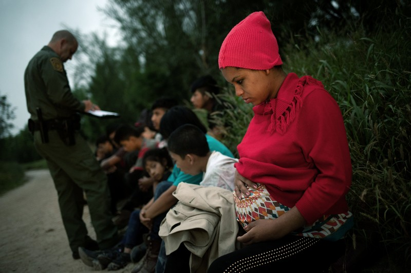 A pregnant woman and other migrants are apprehended by a Border Patrol agent