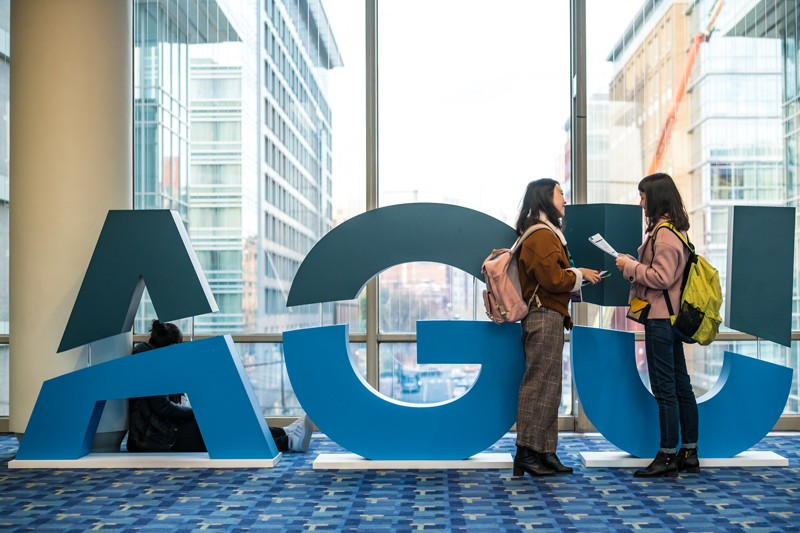 Women stand by and AGU sign at the AGU's 2018 Fall Meeting