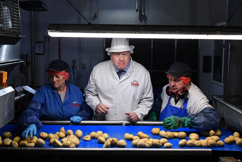 Boris Johnson helps quality control staff during a general election campaign visit to the Tayto Castle crisp factory