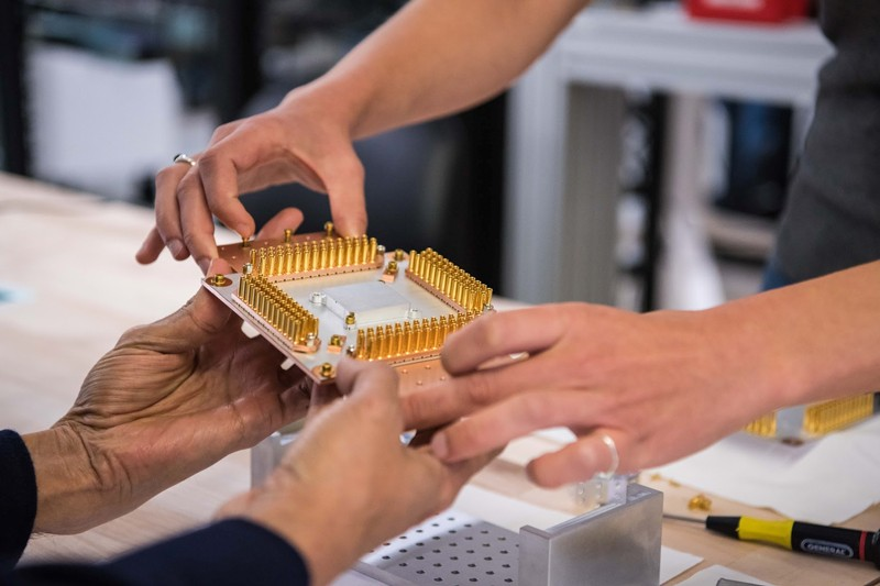 Workers handle a component of Google's Quantum Computer in the Santa Barbara lab, California, U.S.