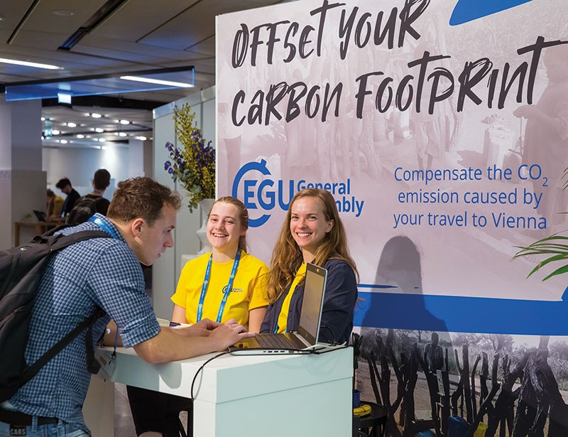 A conference attendee talks to some people on a stand promting how to offset your carbon footprint