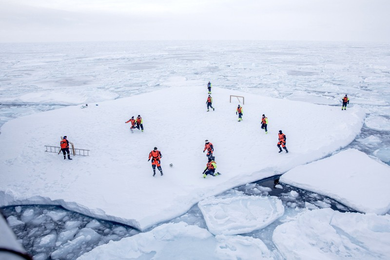 Norwegian Navy privates and scientists from Norwegian Institute of Marine Research, play soccer on an ice floe around Greenland