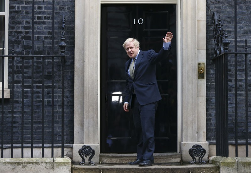 Boris Johnson, U.K. prime minister, waves to the media as he arrives at number 10 Downing Street, on Friday, Dec. 13, 2019.