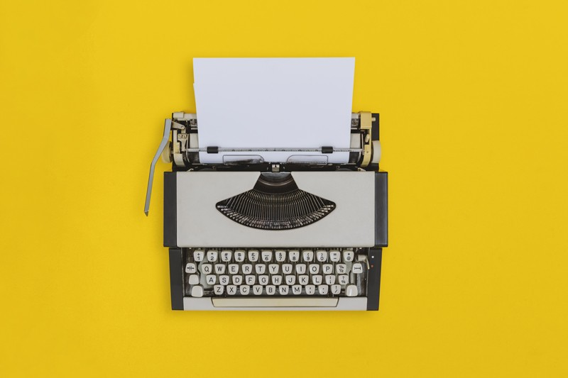 Overhead view of old typewriter on yellow background