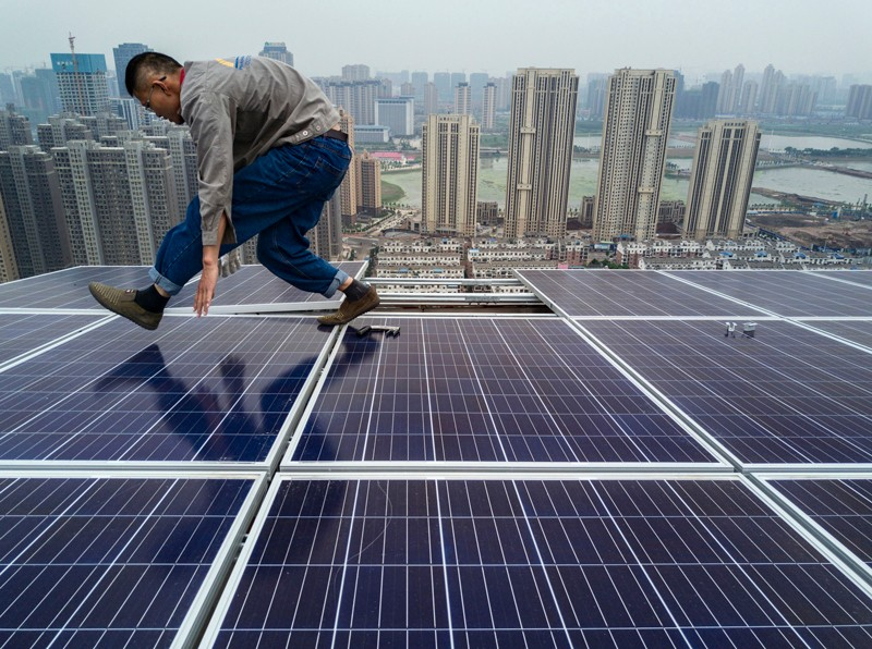 A Chinese worker installing solar panels on the roof of a 47 story building in Wuhan, China