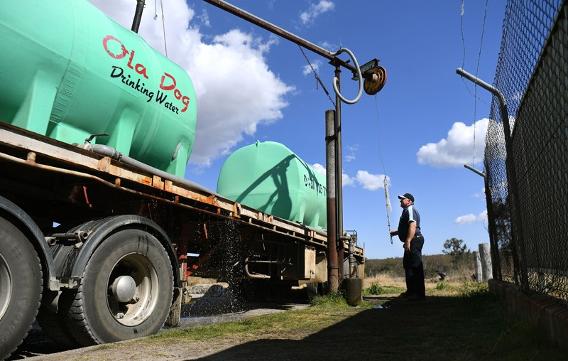 A man fills a tanker with potable water during a drought in Queensland, Australia