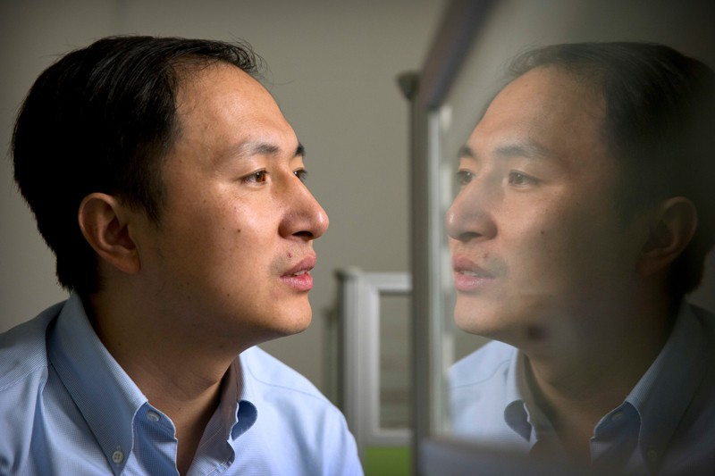He Jiankui is reflected in a glass panel