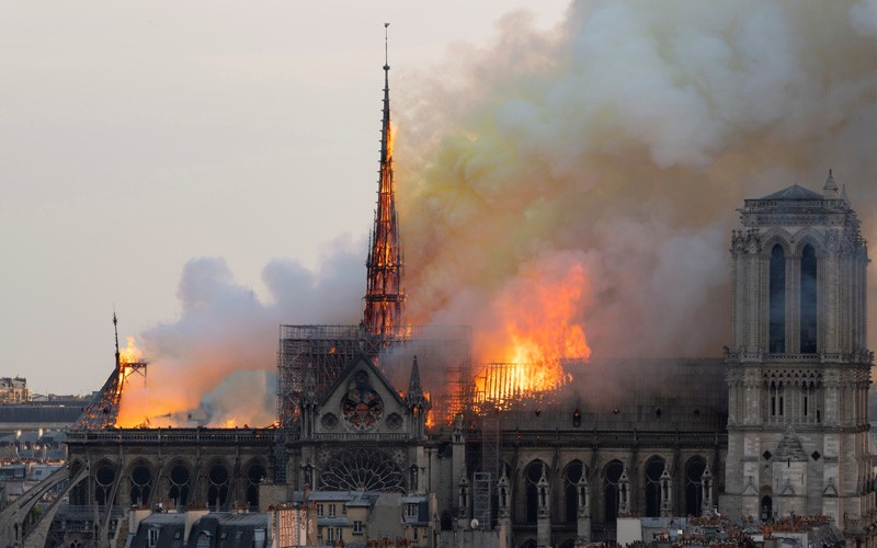 Smoke billows as flames burn through the roof of the Notre-Dame de Paris Cathedral on April 15, 2019.