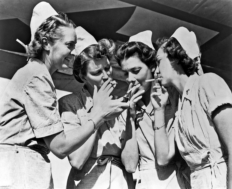 Black and white photo of four US Army nurses sharing a light for their cigarettes.