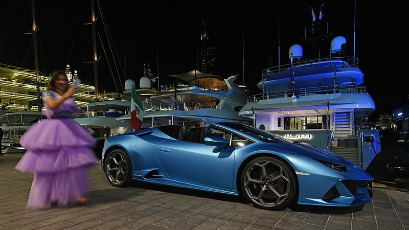 A woman in a lilac ball gown standing next to a blue Lamborghini at a marina, in front of several yachts, at night.