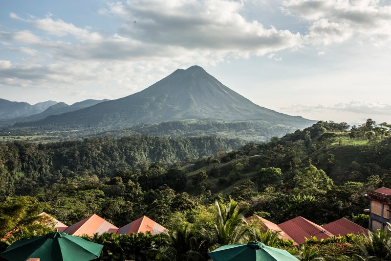 Landscape shot of the Arenal Volcano in Costa Rica surrounded by rainforest with the building roofs in the foreground
