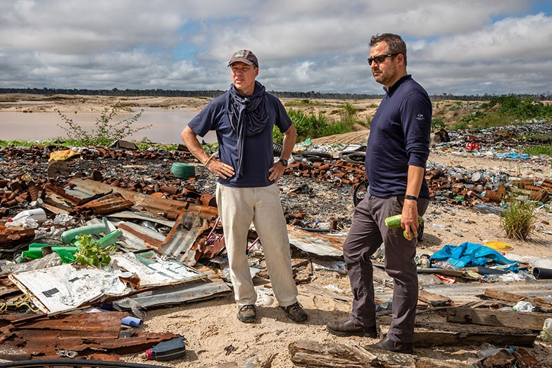Miles Silman (L) and Luis Fernandez (R), from Wake Forest University, survey trash left at the illegal La Pampa gold miners