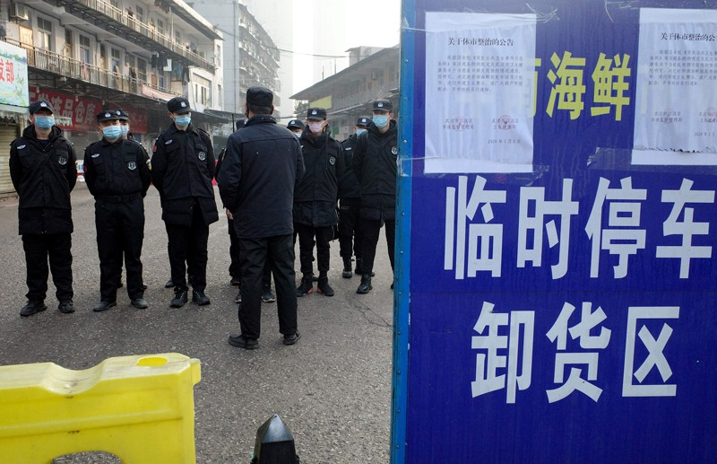 Security guards stand in front of the closed Huanan wholesale seafood market, Wuhan, China.