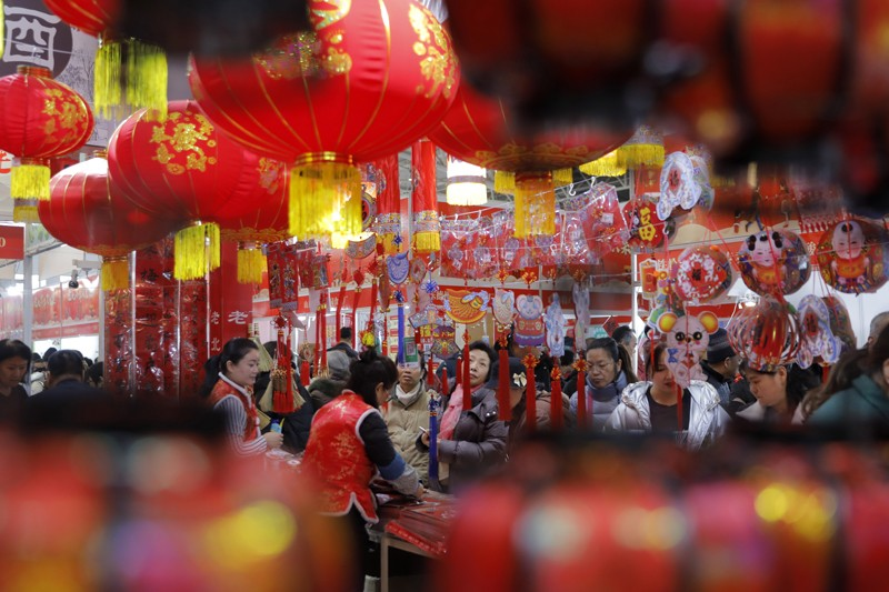 People shop for decorations for the upcoming Chinese Lunar New Year at a market in Beijing, China