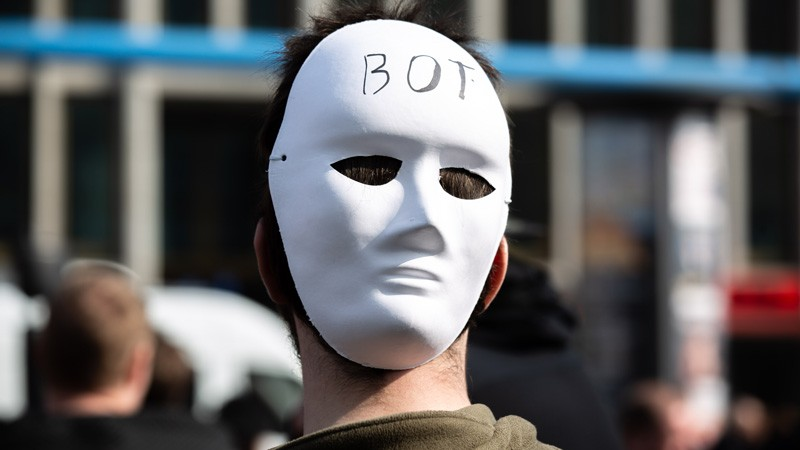 A protestor wears a mask with the writing BOT during the 'Save The Internet' demonstration in Berlin, Germany, 23 March, 2019.