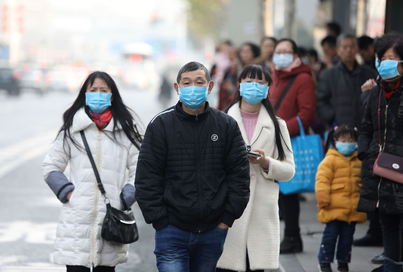 A queue of Chinese people wearing blue face masks.