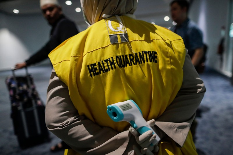 An Indonesian health quarantine official holds a thermal scanner, Soekarno-Hatta International Airport, Indonesia