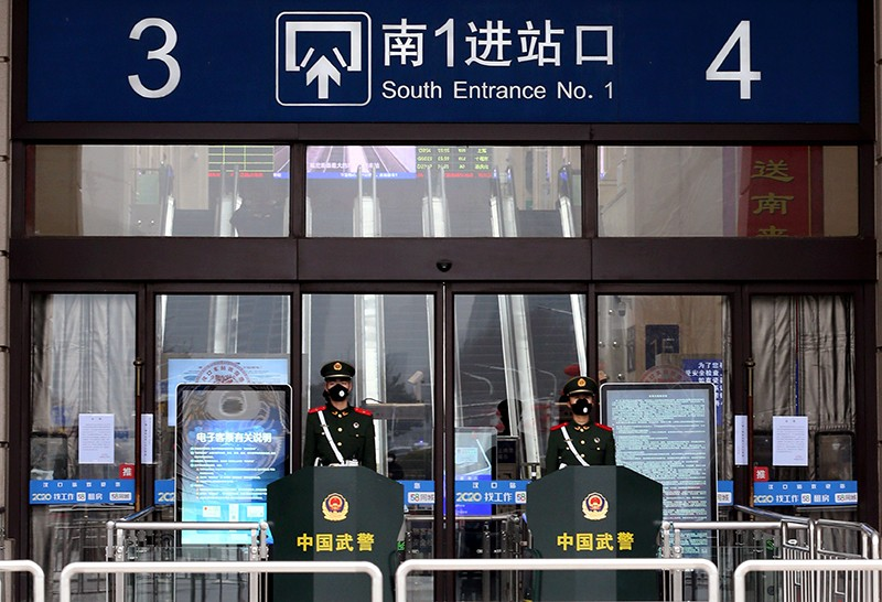Chinese paramilitary officers wearing masks stand guard at an entrance of the closed Hankou Railway Station in Wuhan.
