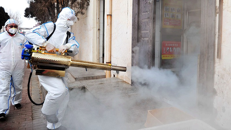 A Qingdao Coronavirus volunteer in a protective suit disinfects a neighborhood in Qingdao, China.