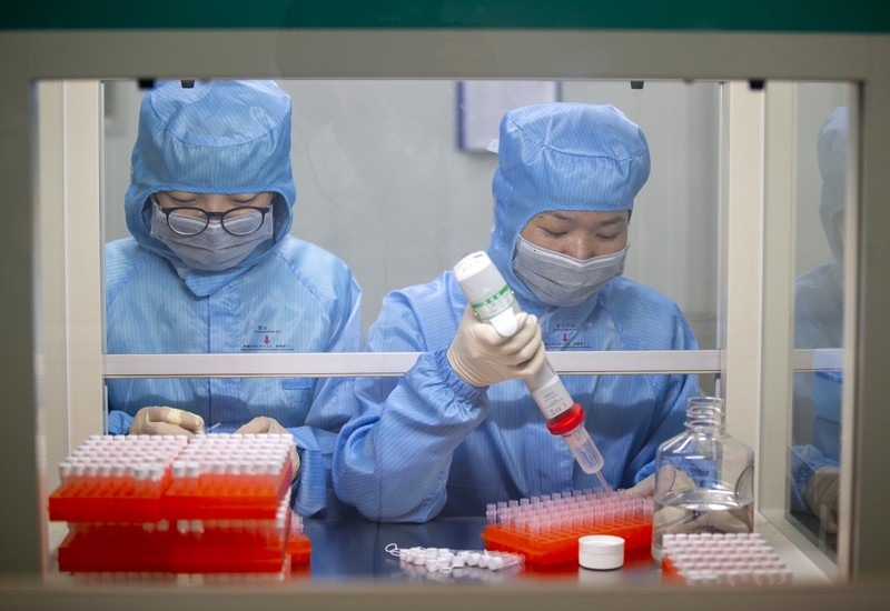 Jiangsu Shuoshi Biotechnology Co. Ltd. production workers working on a coronavirus nucleic acid detection kit, China