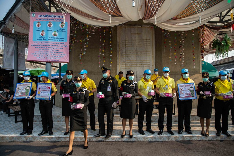 Thai officials standing in a line hand out face masks in Bangkok