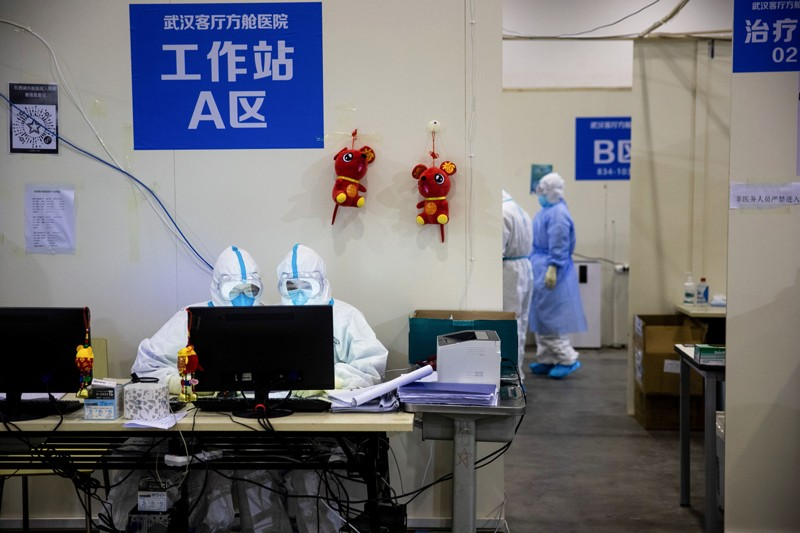 Medical staff members working at a computer in an exhibition centre converted into a hospital in Wuhan, China