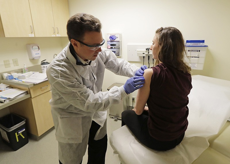 A pharmacist gives a shot to a woman in the first-stage safety study clinical trial of a potential vaccine for the coronavirus