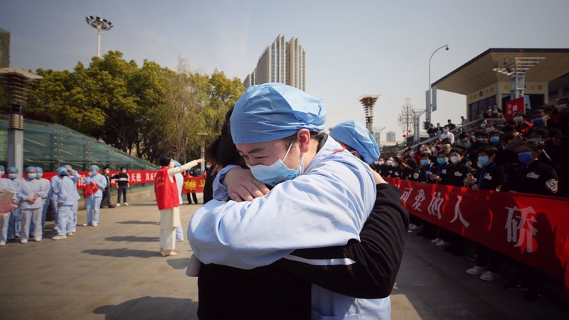 A medical worker (R) embraces a member of a medical assistance team from Jiangsu province.