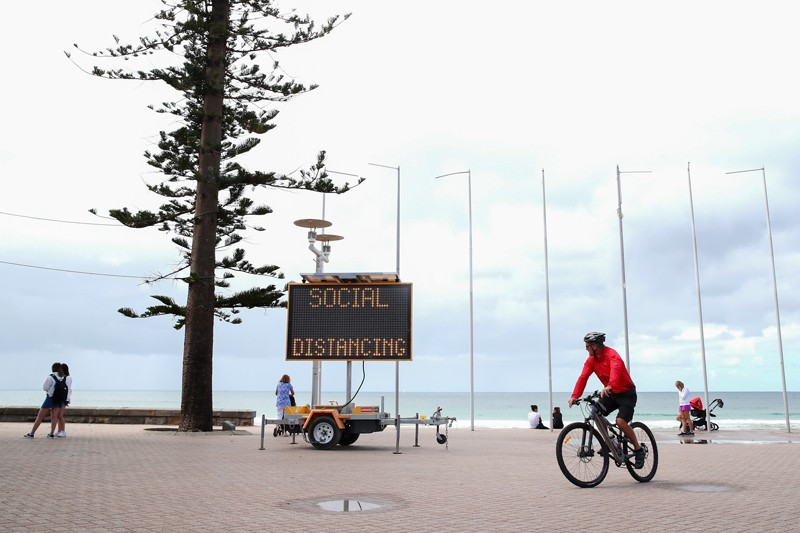 A sign reading 'social distancing' is displayed at Manly Beach