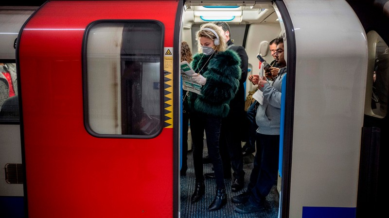 A commuter wears a mask as a precaution whilst travelling on a London Underground.