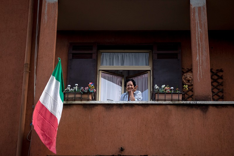 A woman with the Italian flag looks out of her balcony, Rome