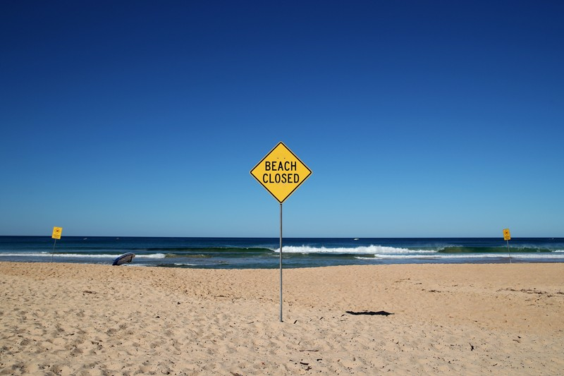 'Beach closed' sign on the desolate North Steyne Beach, Australia