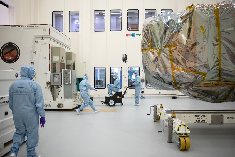 Workers in cleanroom suits move a crate around the Hope probe at The Mohammed Bin Rashid Space Centre