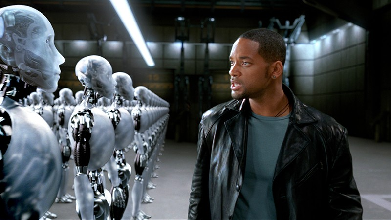 Will Smith looks angrily at lines of translucent robots in a warehouse.