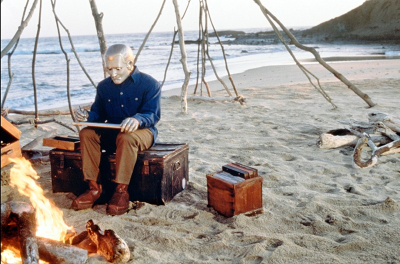 A robot wearing a coat, trousers and shoes sits on a trunk on a beach, next to a campfire.