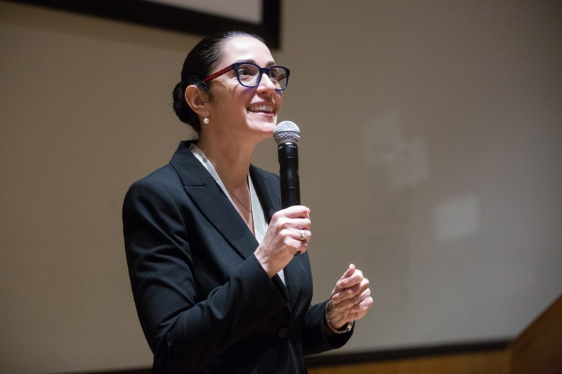 Ruth Gotian speaks into a microphone for a presentation at a conference