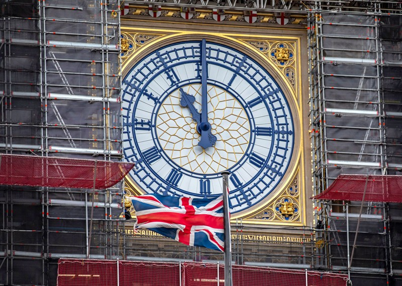 A Union Jack flag flying in front of the clock face of Elizabeth Tower showing 11 o'clock