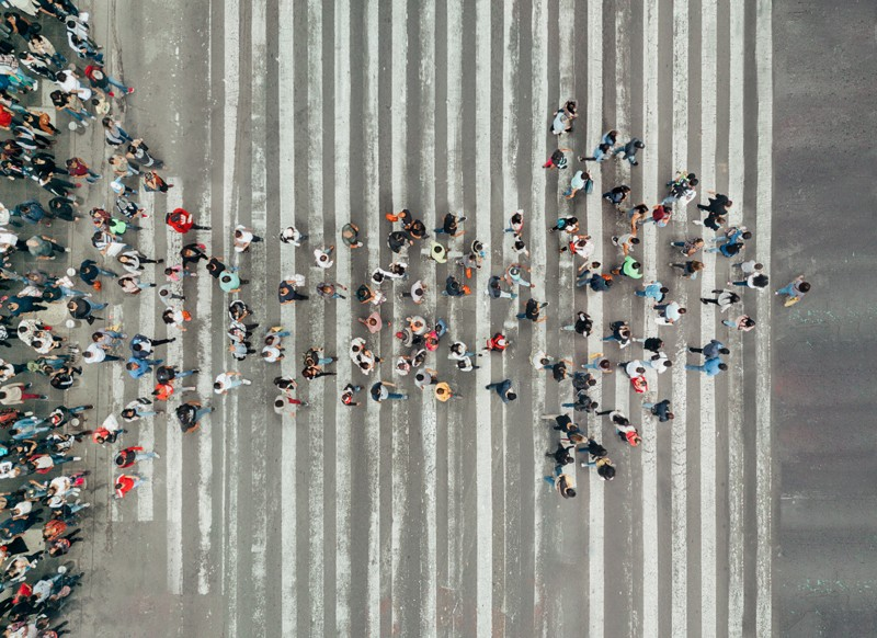 Overhead view of a crowd of people forming the shape of an arrow