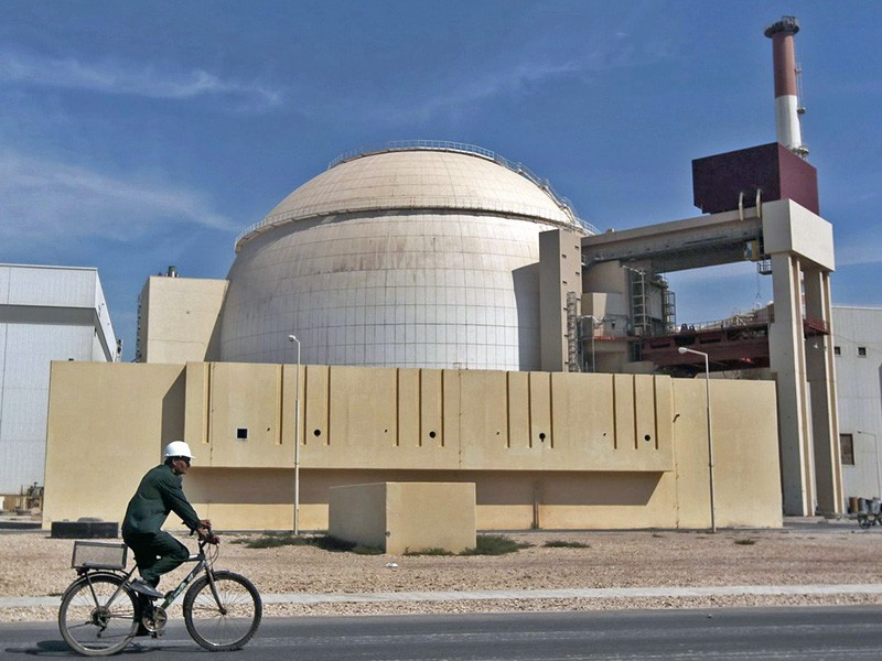 A worker rides a bicycle in front of a reactor building, a white dome behind a concrete wall.