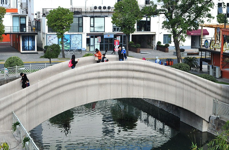 People walk on the 3D-printed concrete pedestrian bridge developed by Tsinghua University (School of Architecture)