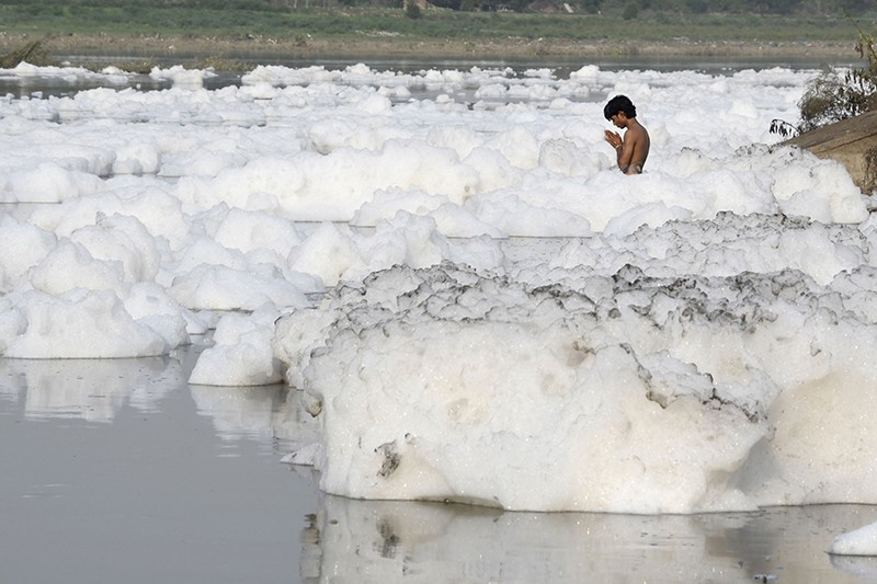 An Indian Hindu devotee prays amongst foam in the polluted Yamuna river in New Delhi, in 2017.