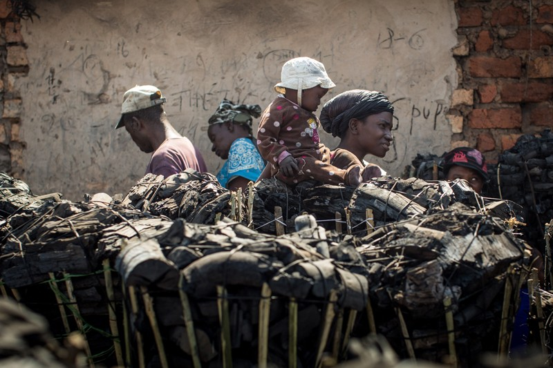 People stand amoung baskets of charcoal bricks at a market in Lubumbashi
