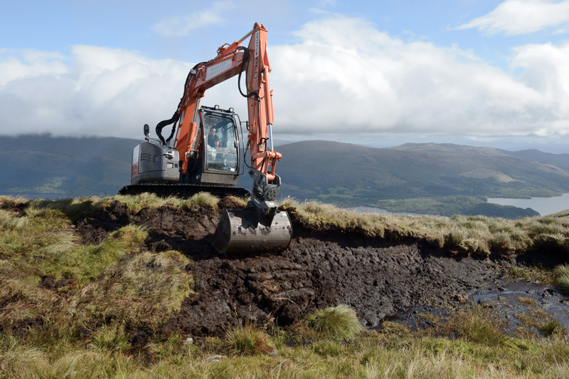An excavator digs up sections of peat on an exposed peat hag