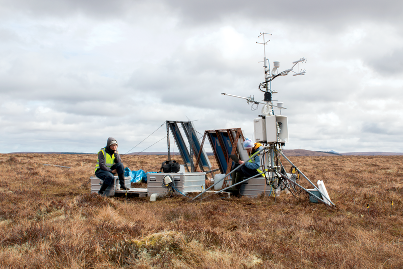 Two researchers sit surrounded by monitoring equipment that make up a Flux tower on an empty blanket bog