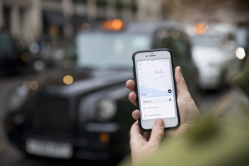 A commuter uses the Uber Technologies Inc. app on a smartphone
