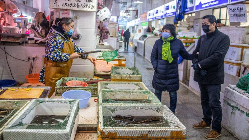 Woman store vendor wearing a mask shows living eel to couple wearing masks at seafood market.